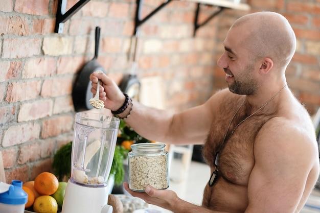 Bell'uomo a torso nudo in cucina