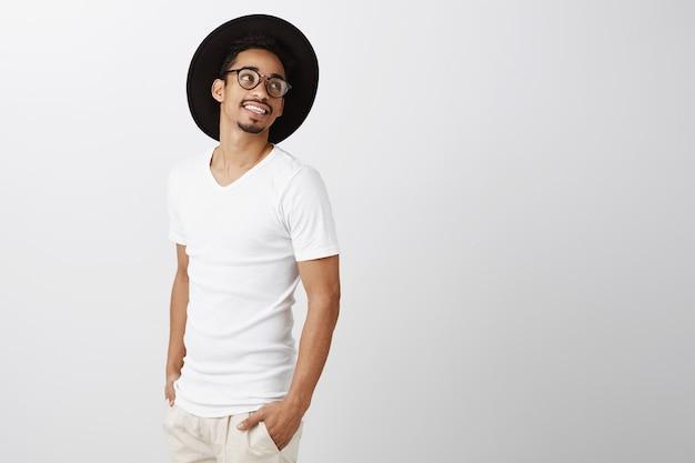 Bell'uomo afroamericano alla moda in occhiali e cappello hipster guardando a destra con un sorriso soddisfatto