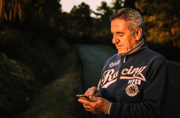 Bell'uomo anziano utilizzando smartphone