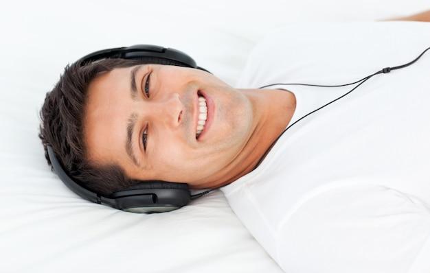 Bell'uomo ascoltando la musica sdraiata sul suo letto