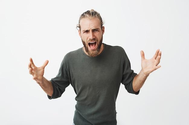 Bell'uomo attraente con acconciatura alla moda e barba urlando