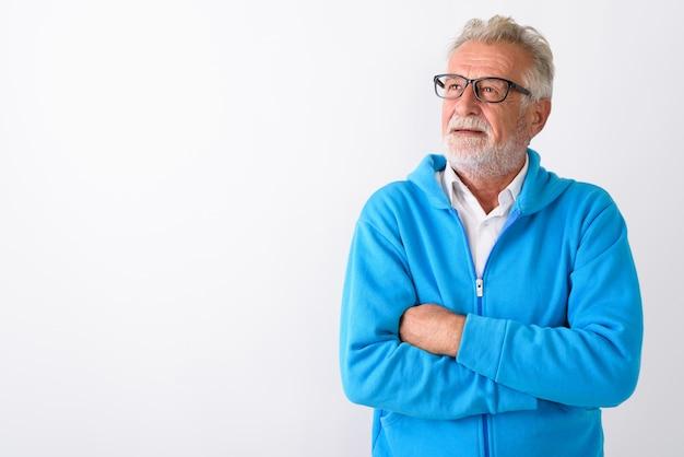 Bell'uomo barbuto anziano che pensa con le braccia incrociate pronto per la palestra su bianco