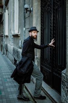 Bell'uomo barbuto con i baffi di ritorno a casa dal lavoro. concetto di movember