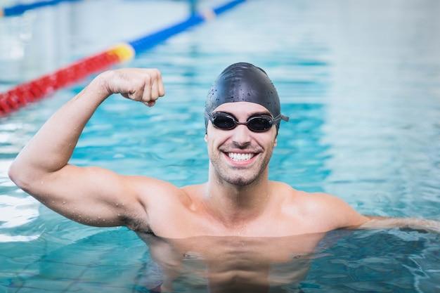 Bell'uomo che trionfa con le braccia alzate in piscina