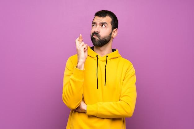Bell'uomo con felpa gialla con le dita che attraversano e che desiderano il meglio