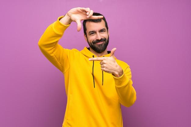 Bell'uomo con felpa gialla messa a fuoco del viso. simbolo di inquadratura