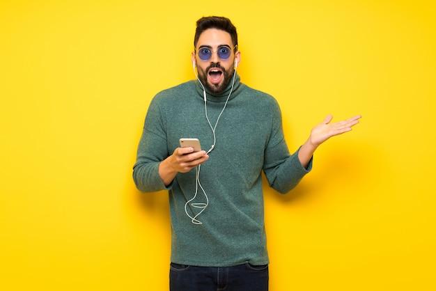 Bell'uomo con gli occhiali da sole sorpreso e l'invio di un messaggio