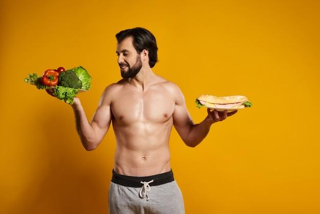 Bell'uomo con il torso nudo detiene verdure e sandwich.