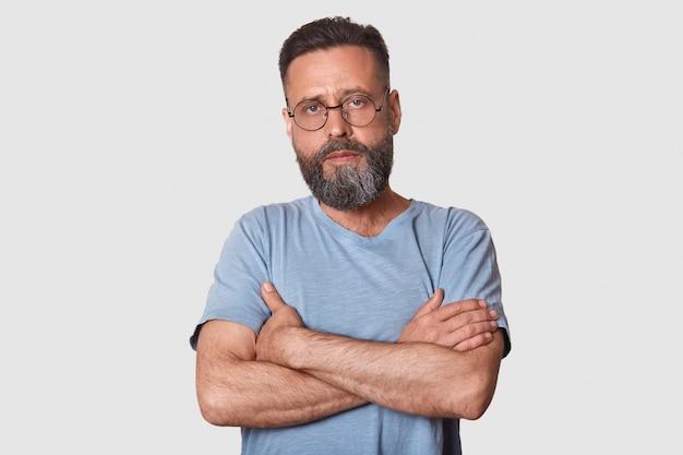 Bell'uomo con la barba in piedi con le braccia conserte isolato su bianco, sembra serio, indossa maglietta grigia casual e occhiali, posa maschile. concetto di persone
