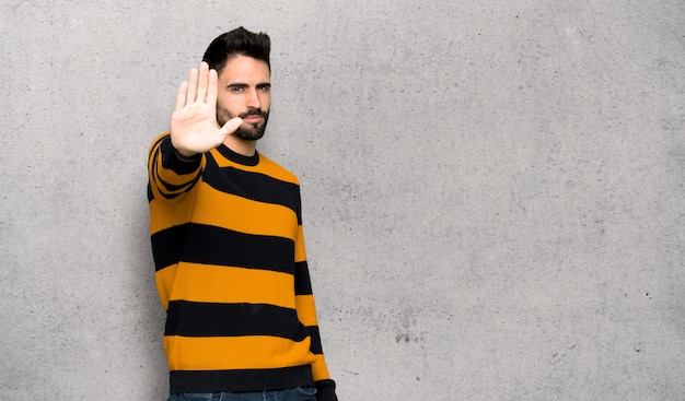 Bell'uomo con maglione a strisce che fa fermare il gesto negando una situazione che pensa che sia sbagliato