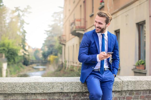 Bell'uomo d'affari con uno smartphone