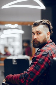 Bell'uomo d'affari in un negozio di barbiere