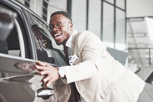 Bell'uomo di colore in concessionaria sta abbracciando la sua nuova auto e sorridendo.