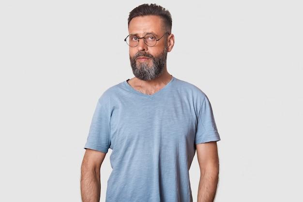 Bell'uomo di mezza età, con grave espressione facciale, abbigliamento casual da uomo e occhiali ottici arrotondati, in posa isolato su bianco.