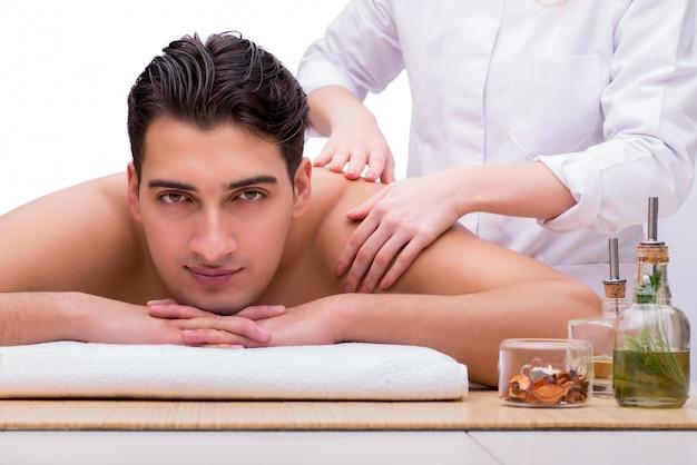 Bell'uomo durante la sessione di massaggio termale