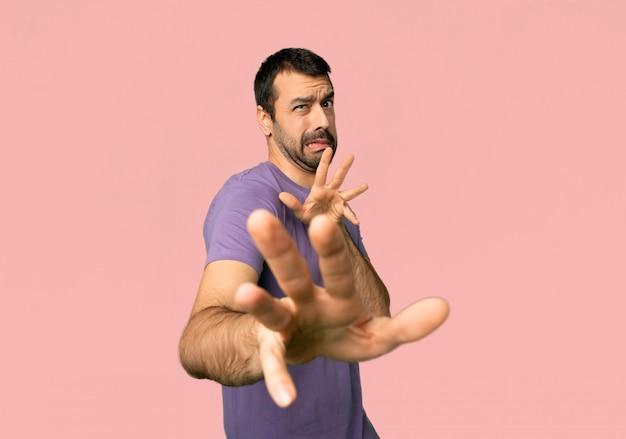 Bell'uomo è un po 'nervoso e spaventato allungando le mani verso la parte anteriore su sfondo rosa isolato