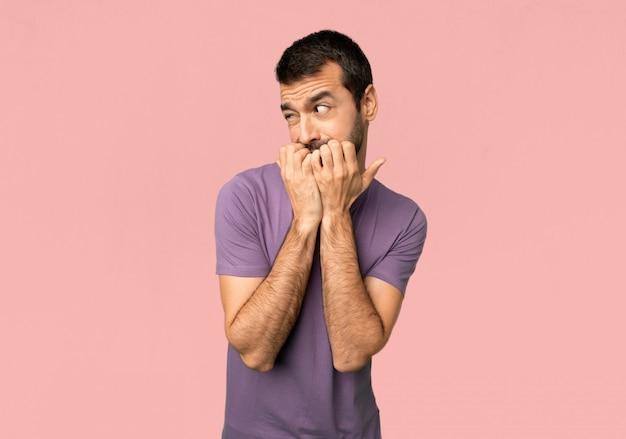 Bell'uomo è un po 'nervoso e spaventato mettendo le mani in bocca su sfondo rosa isolato