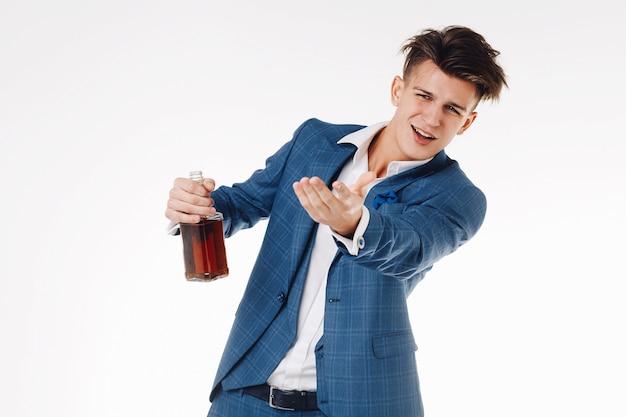 Bell'uomo elegante con una bottiglia di whisky ballare e divertirsi.