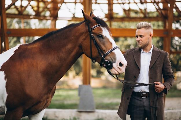 Bell'uomo in completo al ranch a cavallo