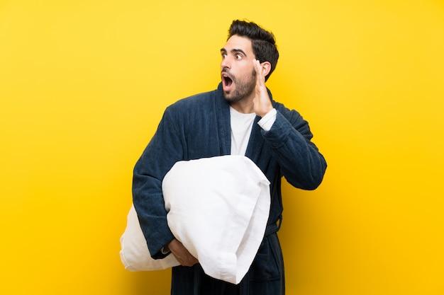 Bell'uomo in pigiama che grida con la bocca spalancata