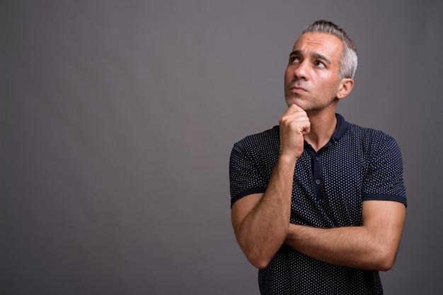 Bell'uomo persiano con i capelli grigi pensando e guardando in alto