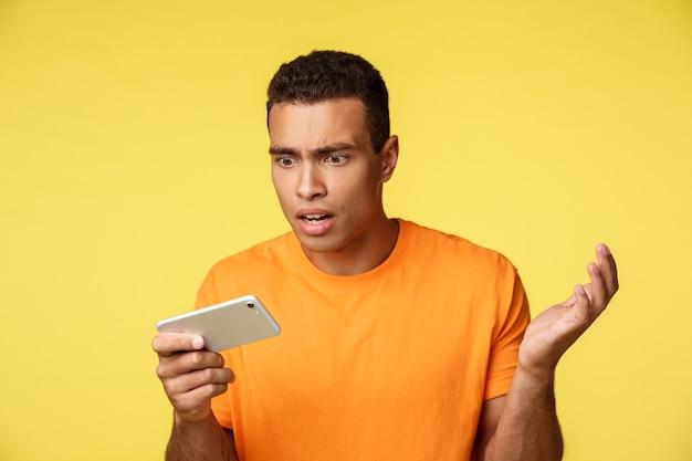 Bell'uomo sconvolto e infastidito, turbato in maglietta arancione, guarda lo schermo mobile interrogato e triste, perdendo, vedi cattive notizie, alza le mani sgomento, leggi risultati sconvolgenti, in piedi sfondo giallo