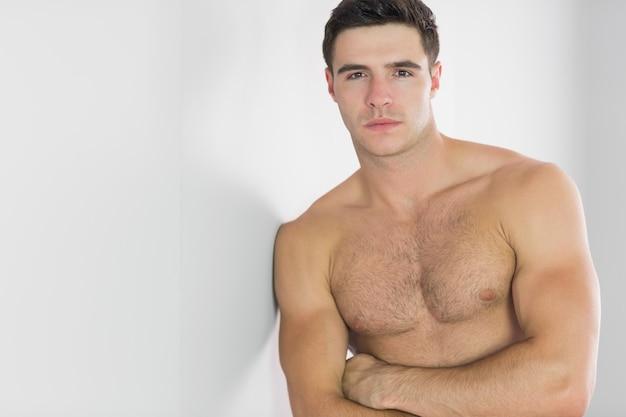 Bell'uomo severo che si appoggia in topless contro la parete