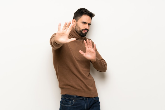 Bell'uomo sopra il muro bianco è un po 'nervoso e spaventato allungando le mani verso la parte anteriore