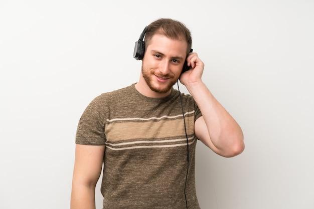 Bell'uomo sopra isolato muro bianco ascoltando musica con le cuffie