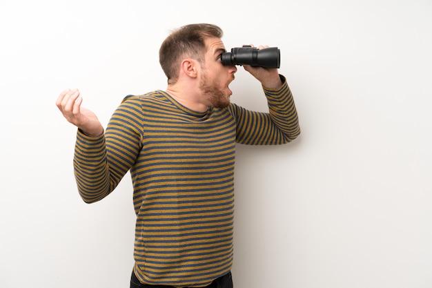 Bell'uomo sopra isolato muro bianco con un binocolo nero