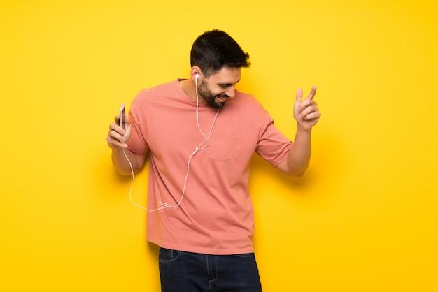 Bell'uomo sopra la musica d'ascolto muro giallo con il telefono
