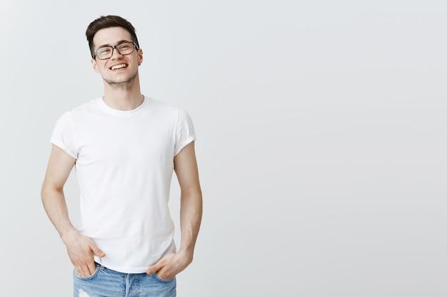 Bell'uomo sorridente in bicchieri in piedi