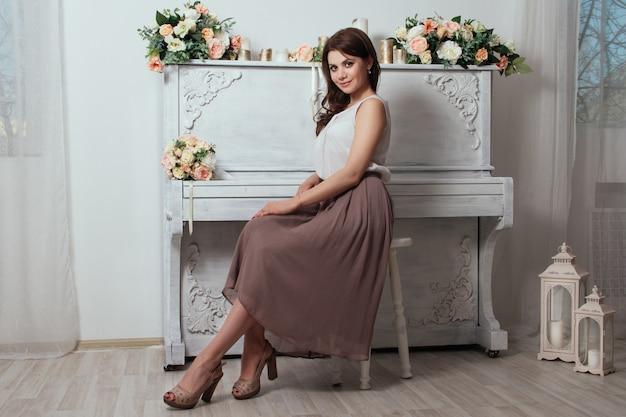 Bella affascinante brunetta in casa vicino al vecchio pianoforte su cui giacciono mazzi di rose