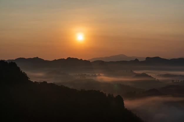 Bella alba e cielo colorato nella nebbia sopra la montagna