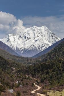 Bella alba nuvolosa nelle montagne con la cresta della neve