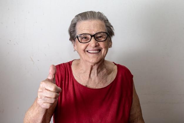 Bella anziana con due tumbs in su. anziano caucasico allegro che mostra due pollici su su fondo bianco.