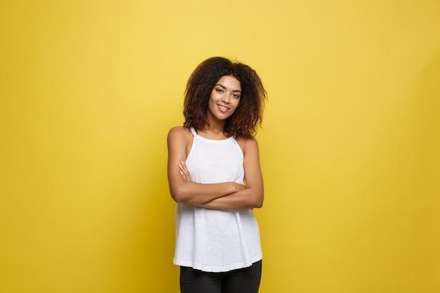 Bella attraente donna afroamericana postando giocare con i capelli ricci afro. sfondo di studio giallo. copia spazio.