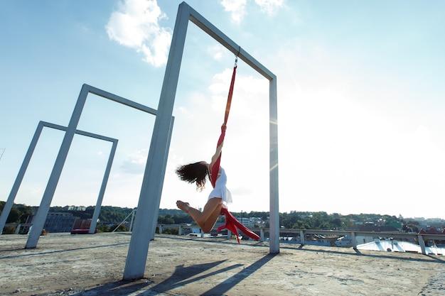 Bella ballerina aerea, danza di seta sul tetto al sorgere del sole
