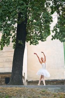 Bella ballerina aggraziata che danza per le strade di una vecchia ci