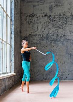 Bella ballerina che balla con il nastro blu