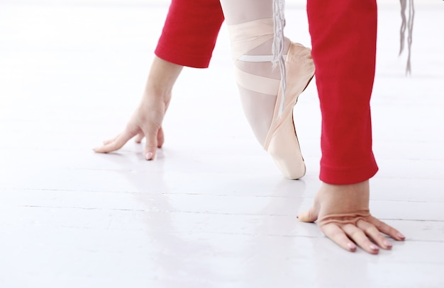 Bella ballerina in rosso in equilibrio su un piede