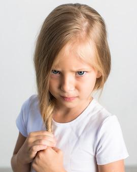 Bella bambina bionda in una maglietta bianca