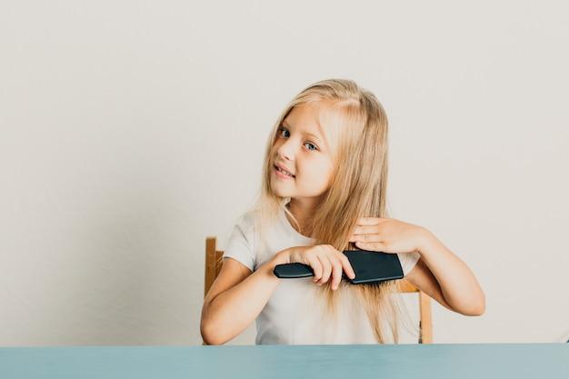 Bella bambina bionda usando un pettine