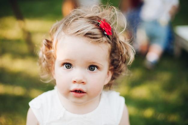 Bella bambina caucasica con capelli biondi ondulati corti in abito bianco in giardino