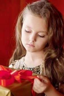 Bella bambina che apre un contenitore di regalo. celebrazioni di natale, capodanno e compleanno.