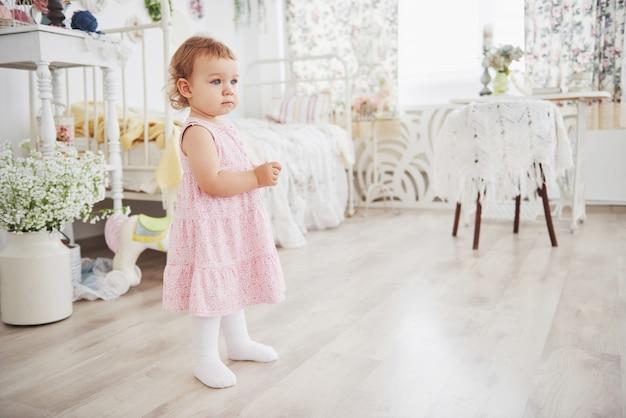 Bella bambina che gioca i giocattoli. bionda dagli occhi blu. sedia bianca. la stanza dei bambini. ritratto di ragazza piccola felice. concetto di infanzia