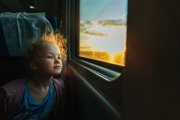 Bella bambina che guarda fuori finestra del treno al di fuori