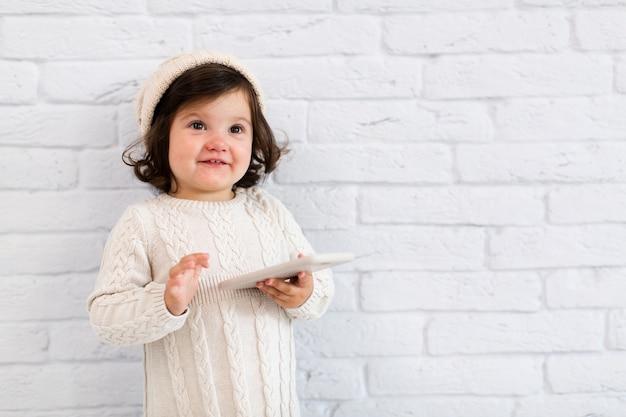 Bella bambina che per mezzo di uno smartphone