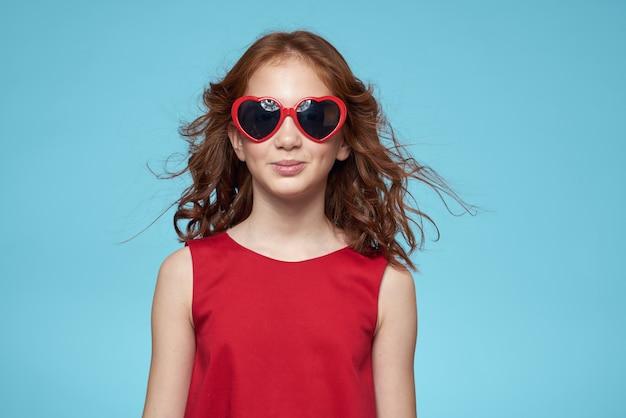 Bella bambina con gli occhiali a cuore e un vestito rosso, principessa, bambino carino