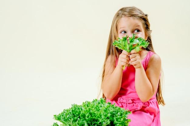 Bella bambina con lattuga in mano su uno sfondo monofonico leggero, corretta alimentazione